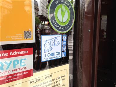 Adesivi sulle vetrine dei negozi di Parigi che aiutano i senza dimora